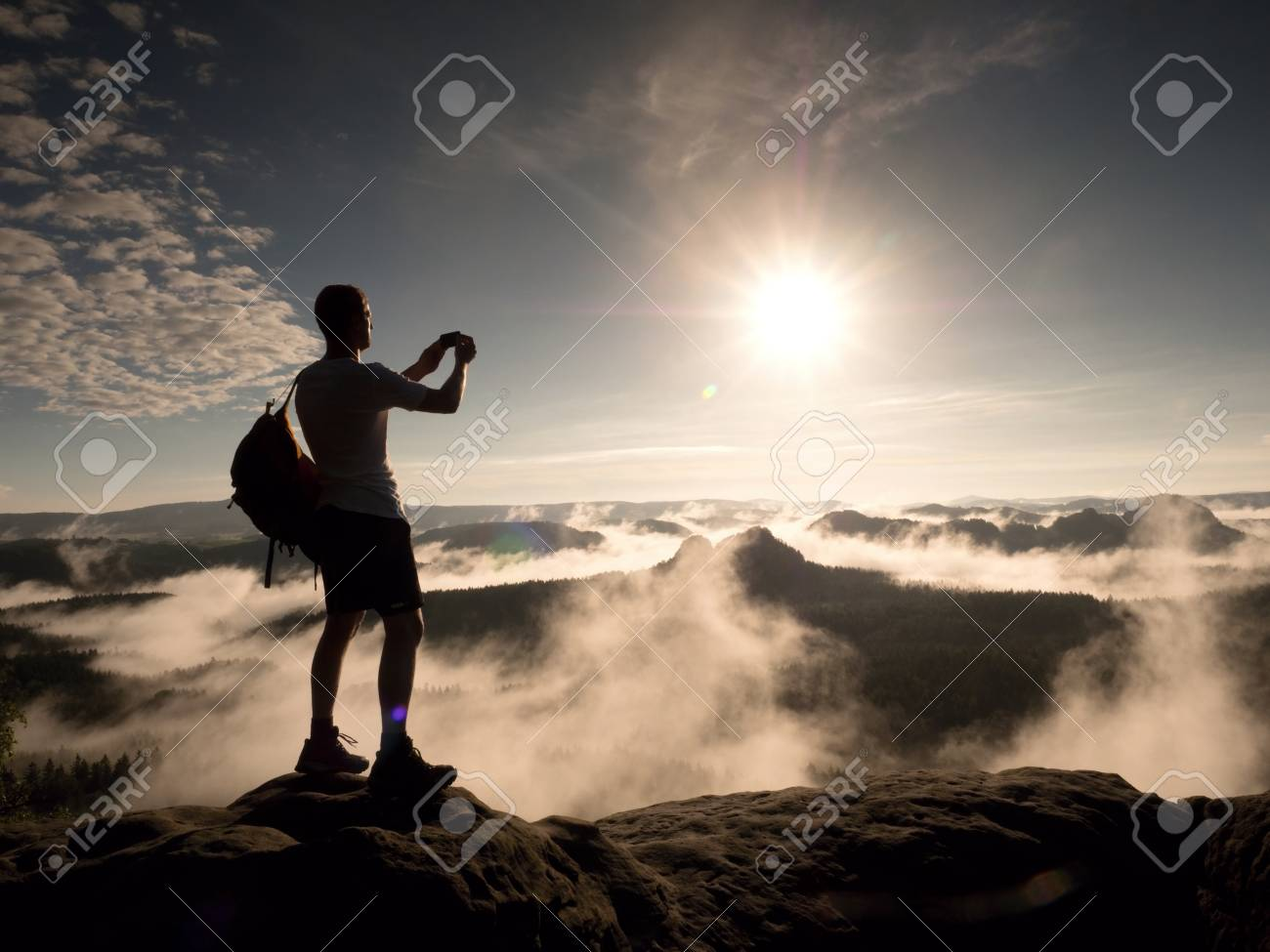 Hiker with backpack reaches the summit of mountain peak  Success,