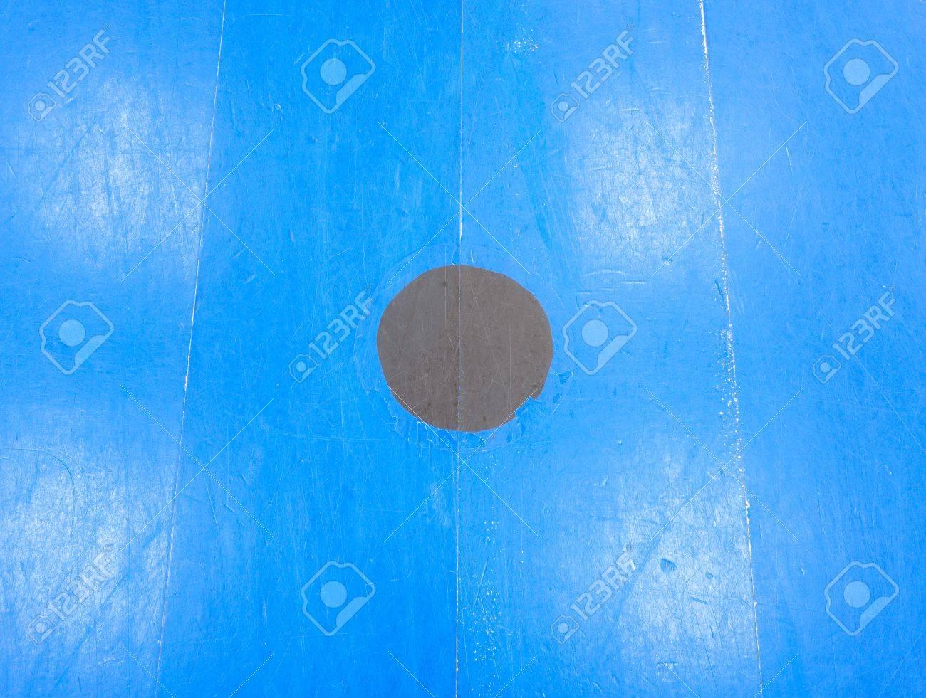 Zwart punt in blauw speelveld. geschilderde houten vloer van