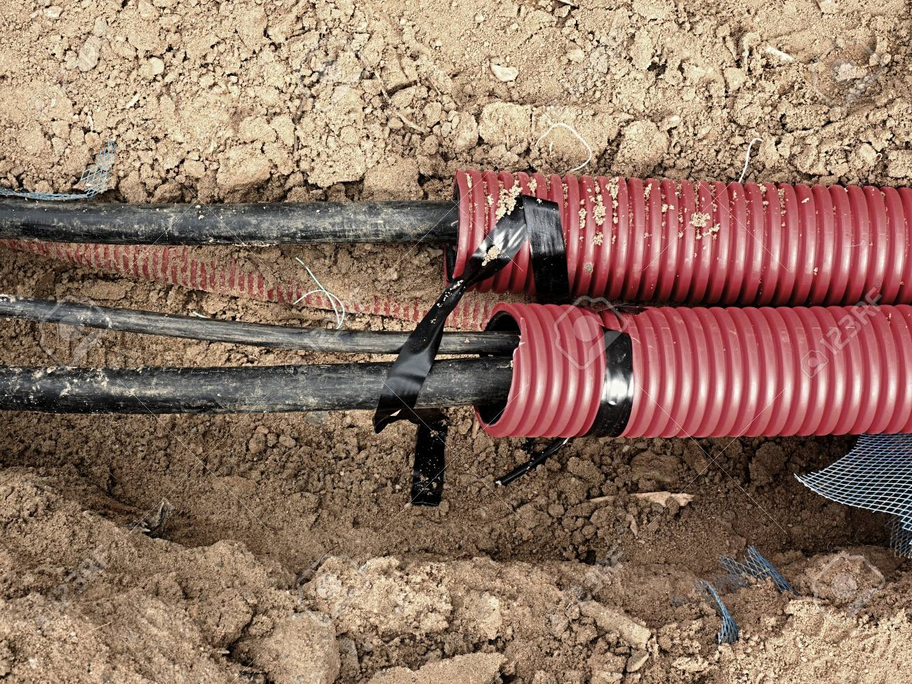 Excavation of trench with black cables in protective HDPE tube. Lines of metallic and fiber optic cables, building of communication optical network. The installation of connection. - 81543406