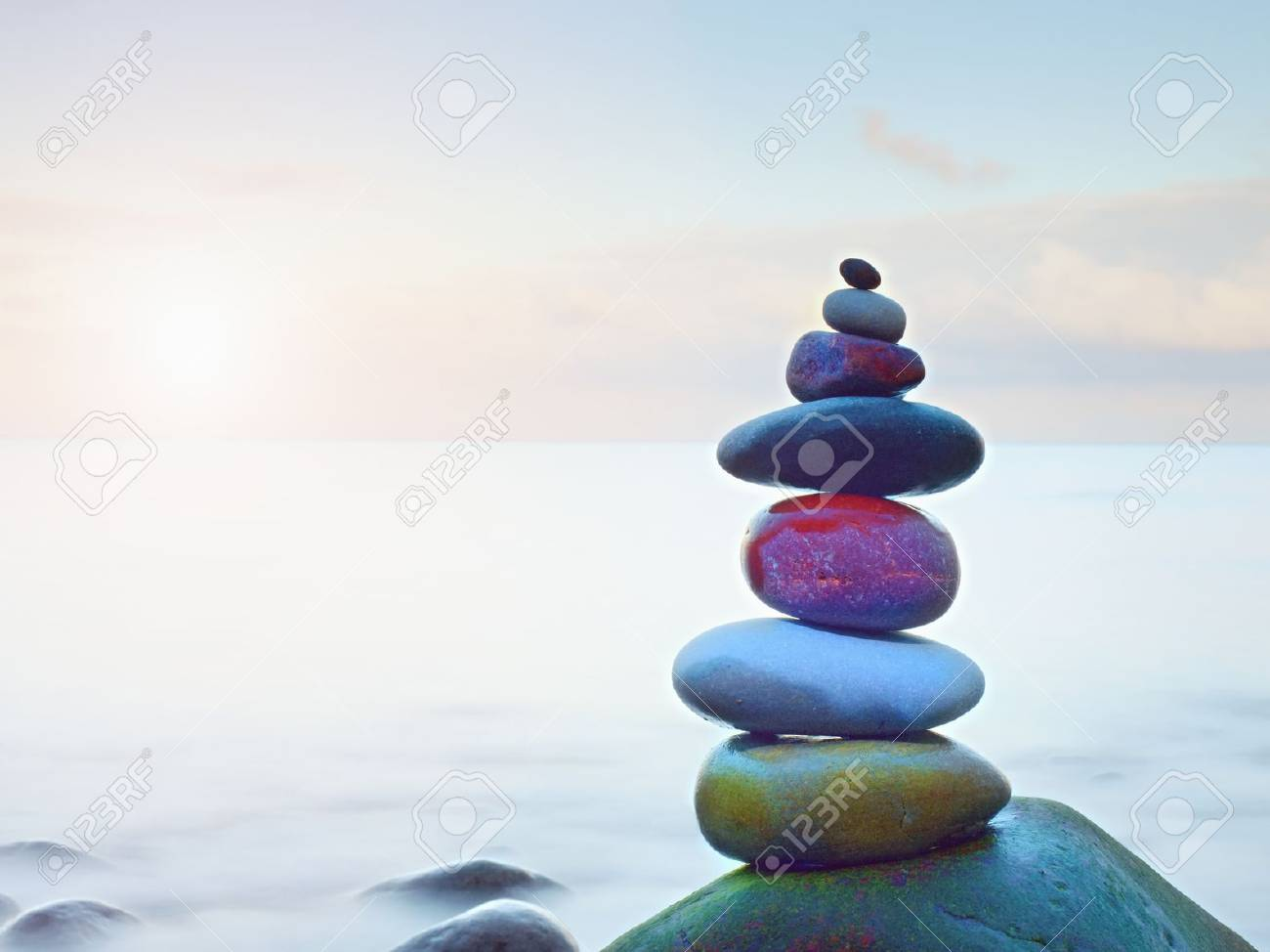 Balanced stone pyramide on shore of blue water of ocean. Blue sky in water level mirror. Poor lighting conditions. - 82196436