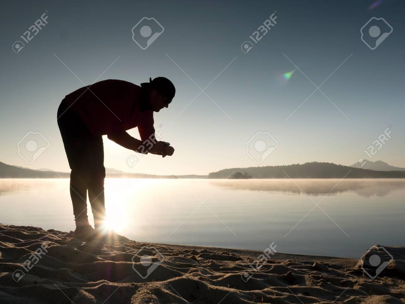 Banque d images - L homme de sport vérifie le temps sur sa montre de sport.  Coureur au lac de montagne exerçant contre le soleil du soir. 0af176f7b21