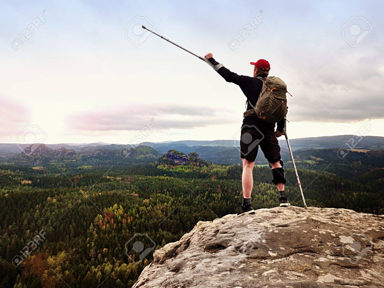 Happy man hiking holding medicine crutch above head, injured knee fixed in knee brace feature. Scenic mountain top with deep cloudy valley below - 83308898