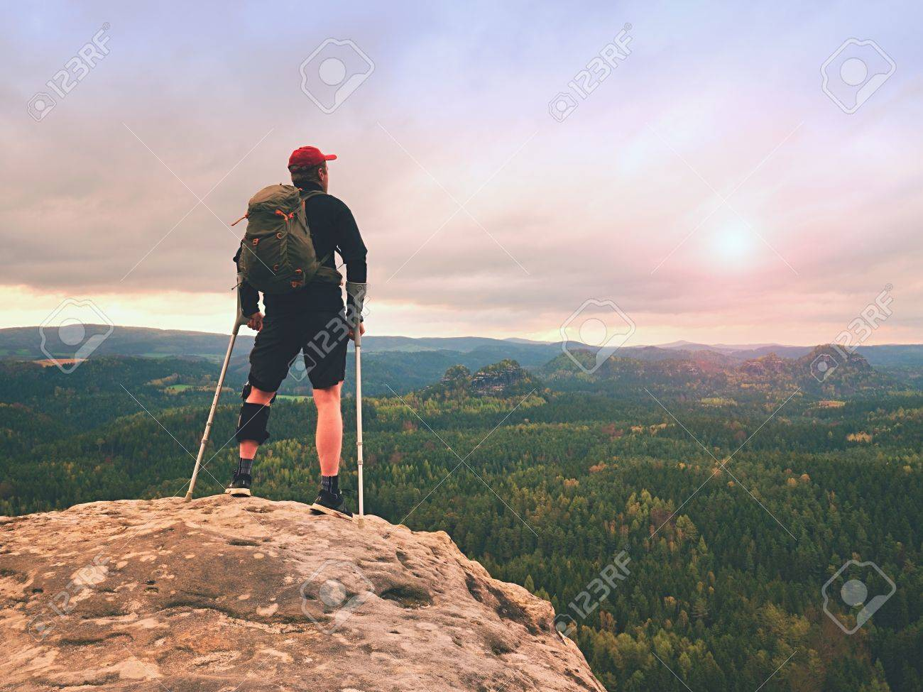 Man hiker Wearing Support Leg Brace and gainst the cruthes. Natural forest park in background - 83308905