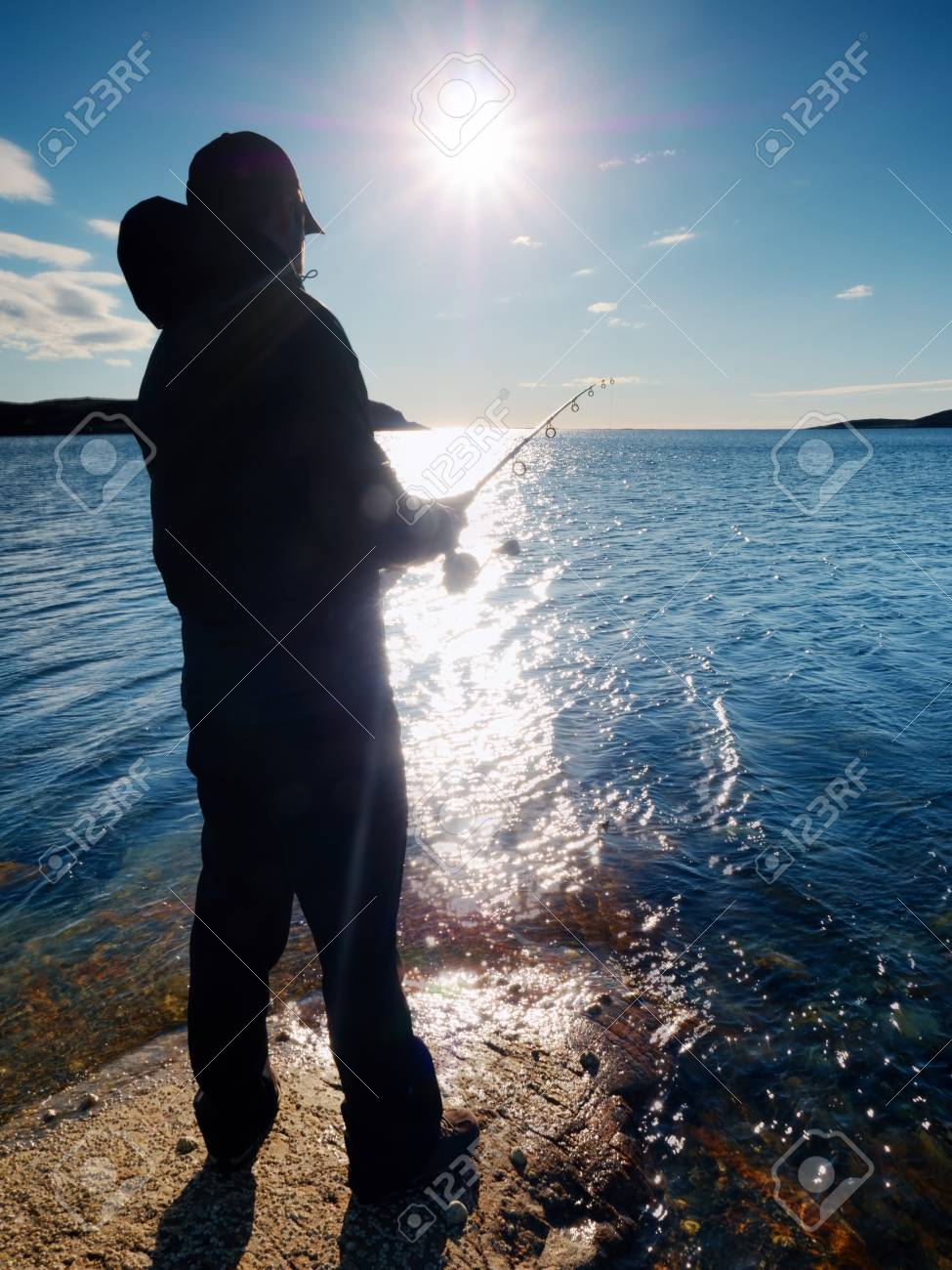 Vista molto vicina del pescatore di lavoro. L uomo controlla l esca di  spinta e lo gettò lontano nel mare. Pescatore con canna da pesca in mano e  si trova ... 1855a88d3bd4