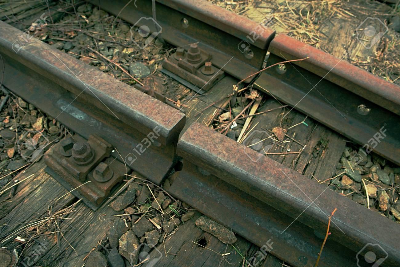 Detail of old rusty rails in abandoned railway station. Rusty train railway detail, granite stones between rails - 96441210