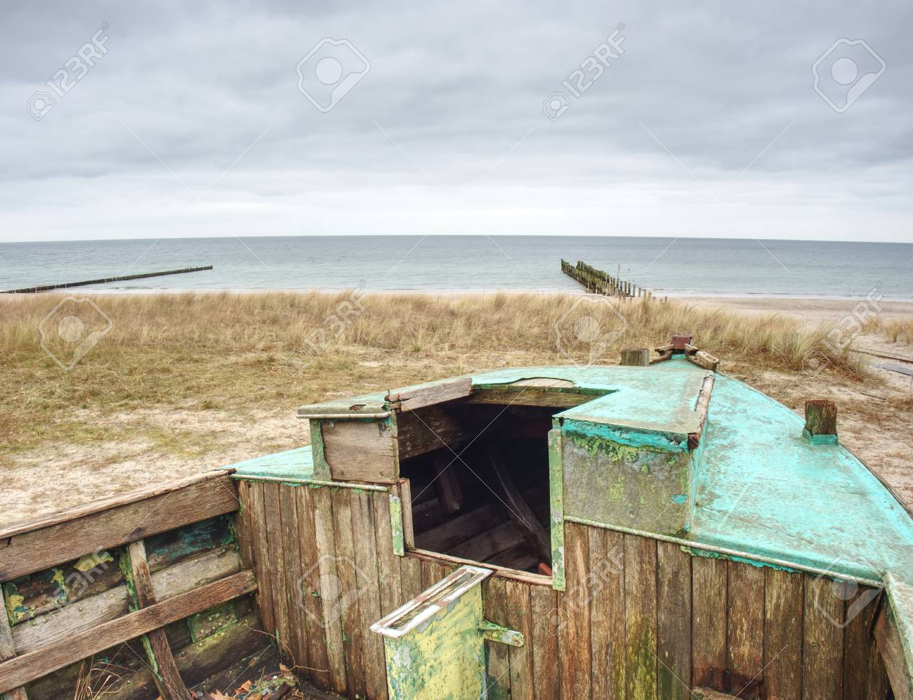 Abandoned wrecked boat stuck in sand  Old wooden boat on the