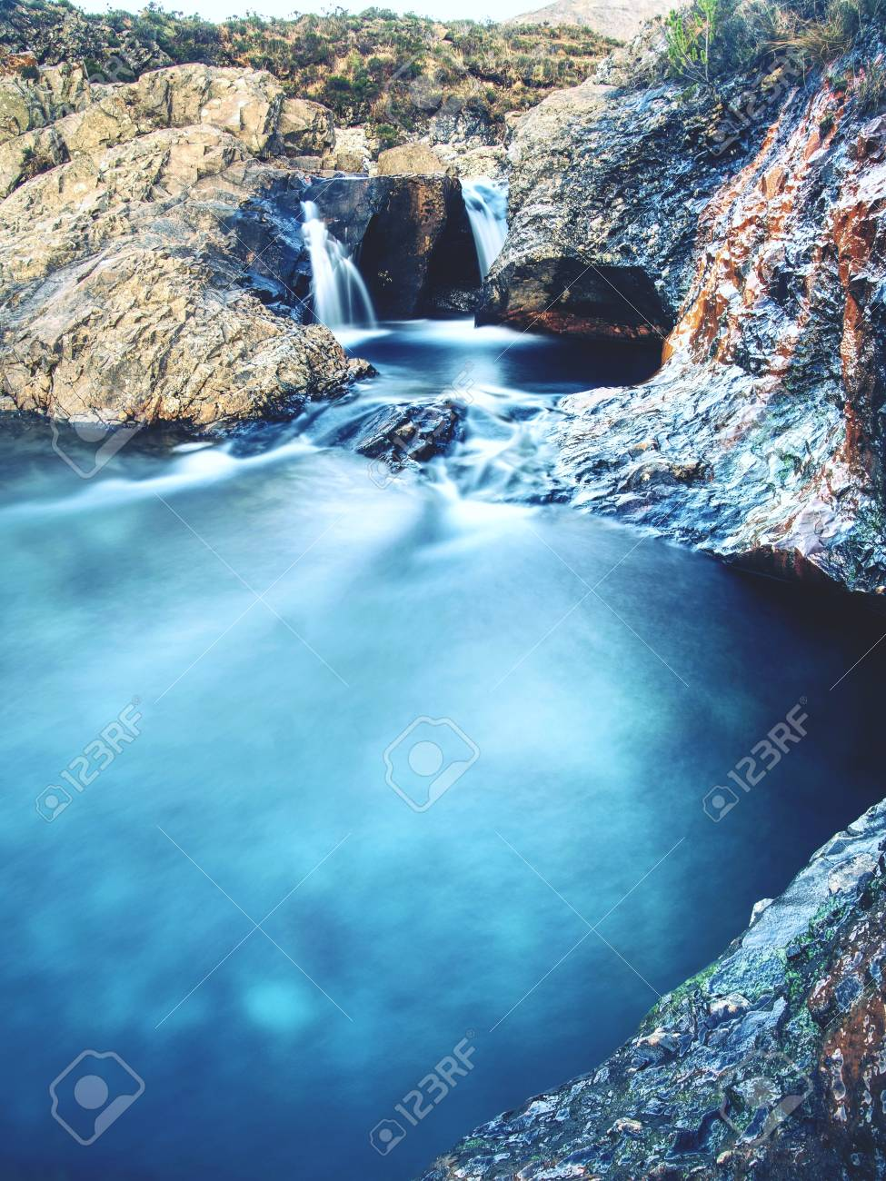 Blue water of river Brittle in trail known as Fairy pools. The mountain river cut in soft rocks colorful pools. Bellow the mountains of Glenbrittle on