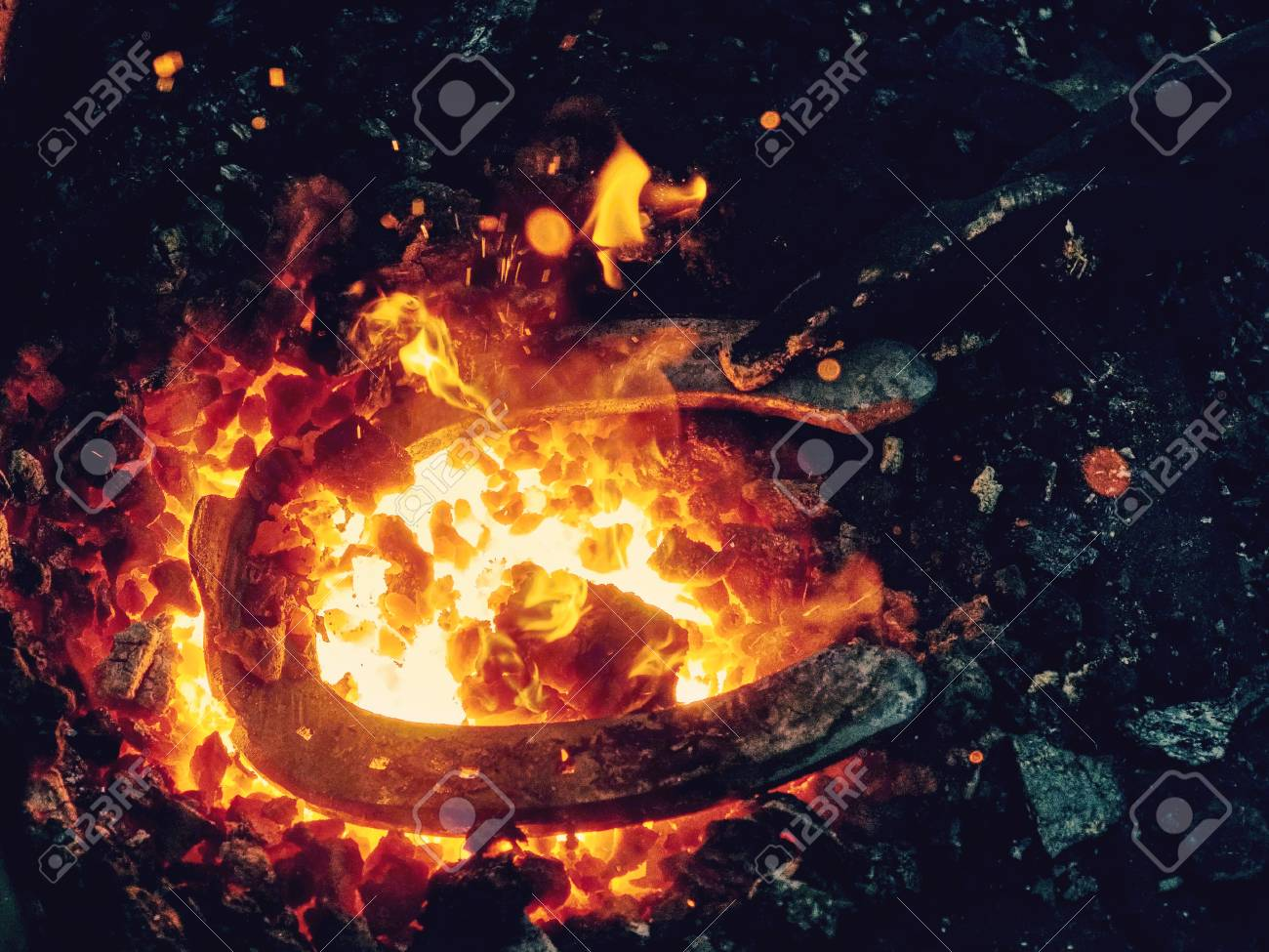 Red fire blazes inside of coal forge. Blacksmith traditional works with hot metal to form horse shoe from semiproduct - 116354876
