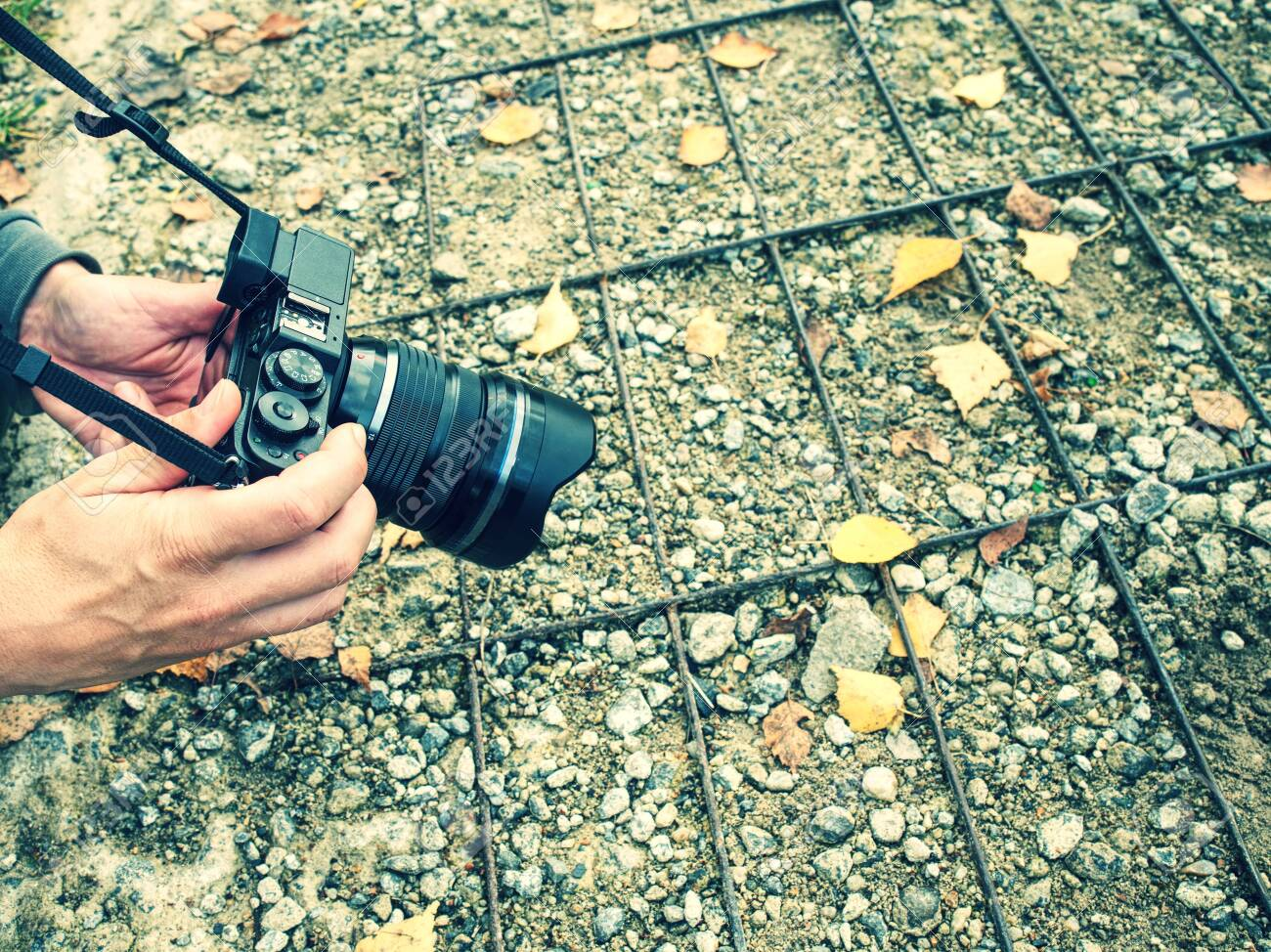 Woman taking pictures with a mirrorless camera in forest in the fall season. Some colorful leaves fallen on the ground in front of camera lens - 132900675