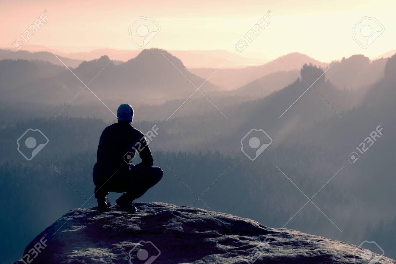 Young man in black sportswear is sitting on cliff's edge and looking to misty valley bellow - 151750050