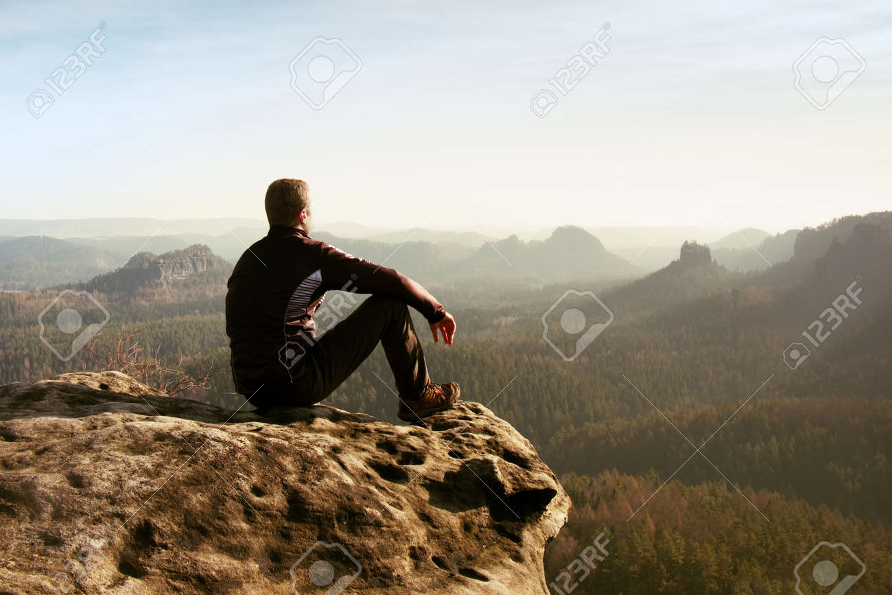 Young man in black sportswear is sitting on cliff's edge and looking to misty valley bellow - 151846175