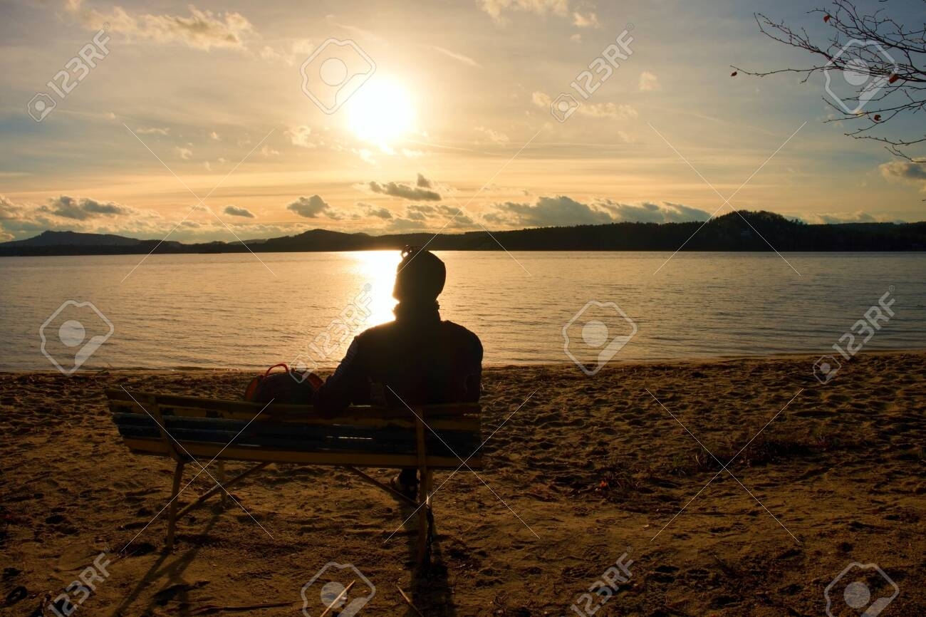 Alone Young Man In Silhouette Sitting In The Sun. Tourist take a rest on the wooden bench at autumn lake. - 152022398