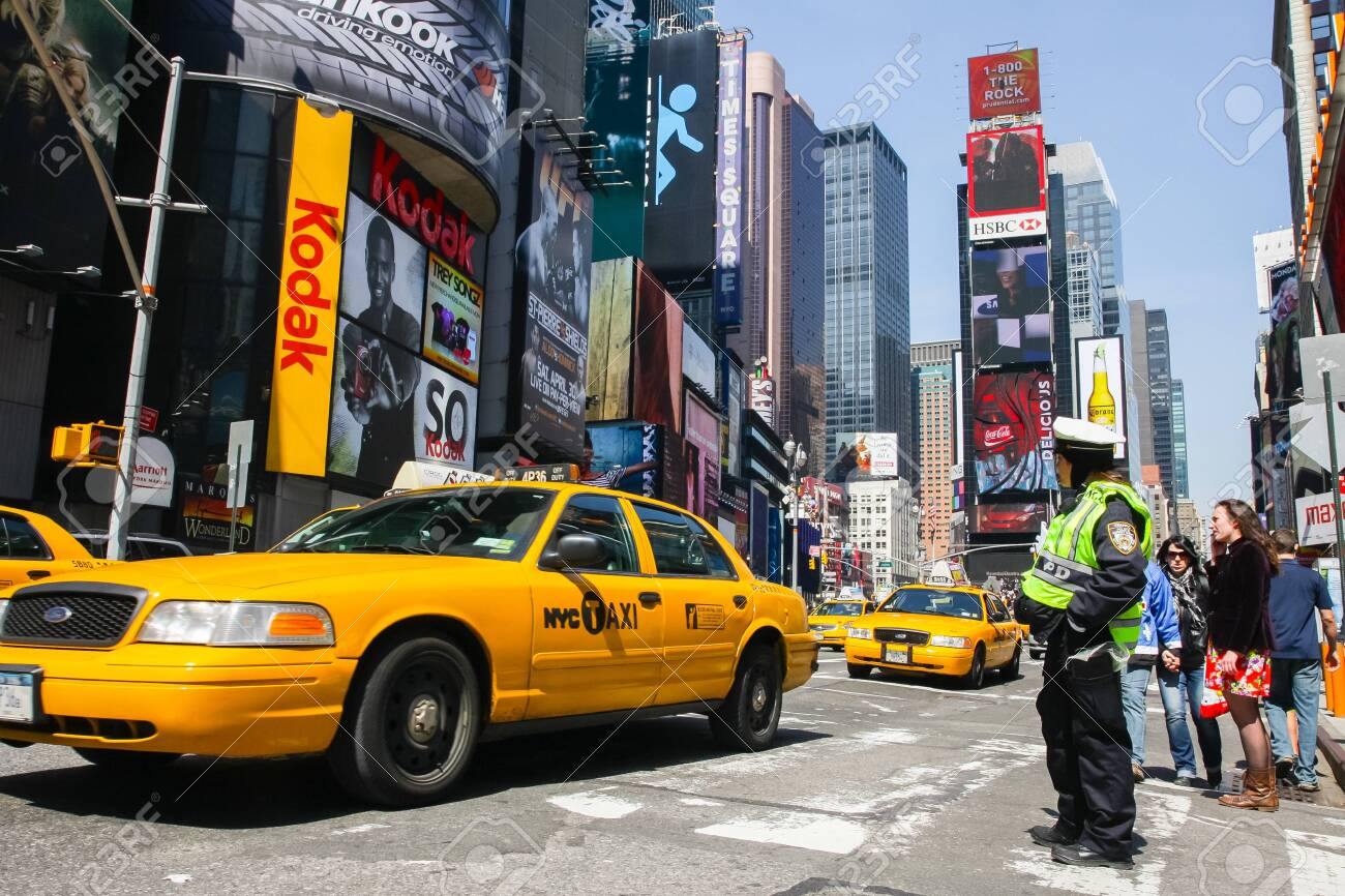 MANHATTAN, NY - February 20, 2011: Yellow Taxi on Broadway at Times Square in Manhattan, New York City with all the lit up billboards and advertisements. - 144457421