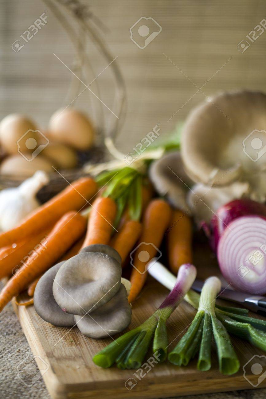 Fresh organic vegetables, eggs, and citrus on a chopping block Stock Photo - 8503917