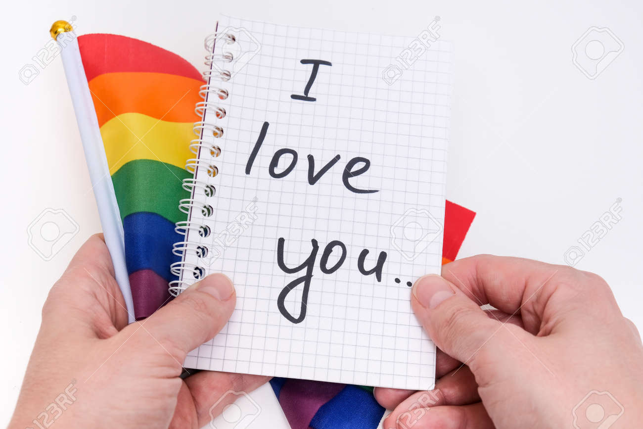 Hands holding a notebook with I Love You inscription and lgbtq rainbow flag on white background - 168193293
