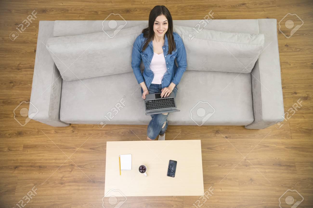 The Happy Woman With A Laptop Sit On The Sofa View From Above Stock