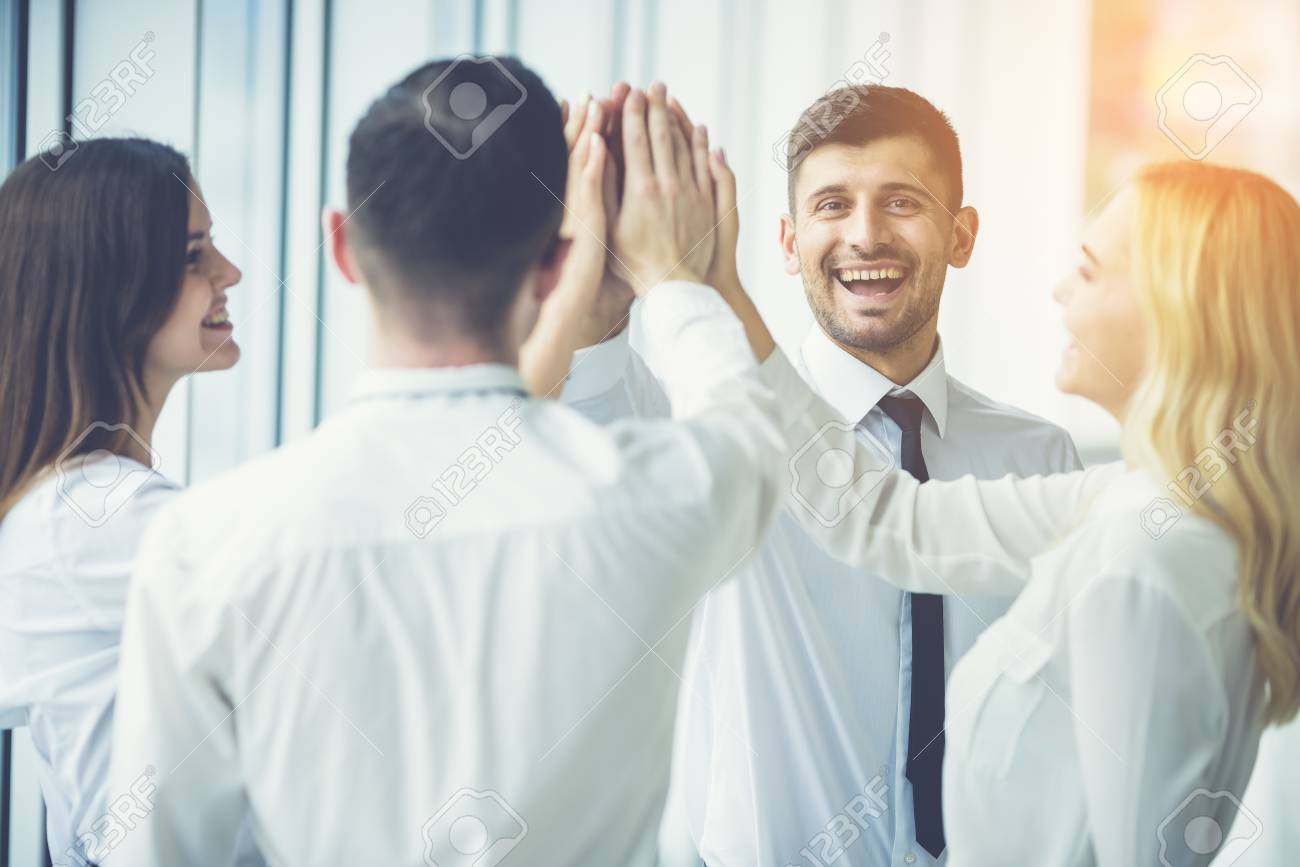 The happy business people greeting with a high five on the sunny stock photo the happy business people greeting with a high five on the sunny background m4hsunfo