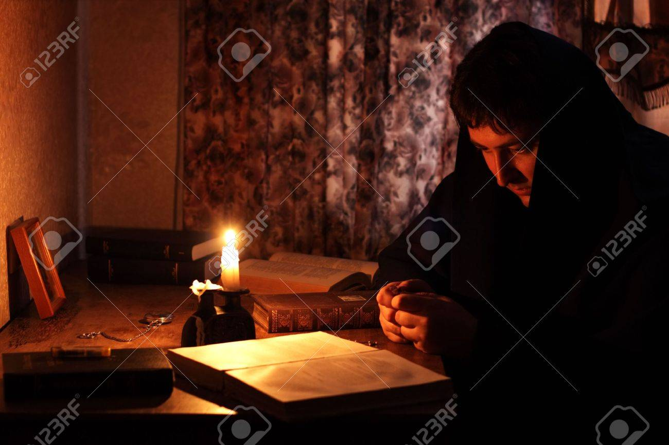 Dark room with candle light - Man Sitting By Candlelight Stock Photo 7406451