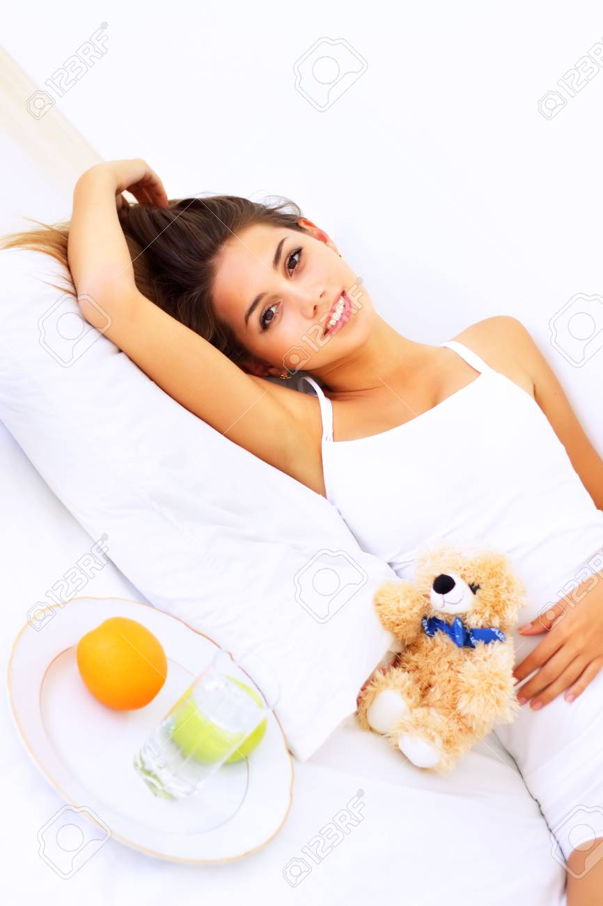 Beautiful girl lying on the bed with a teddy bear Stock Photo - 7706825