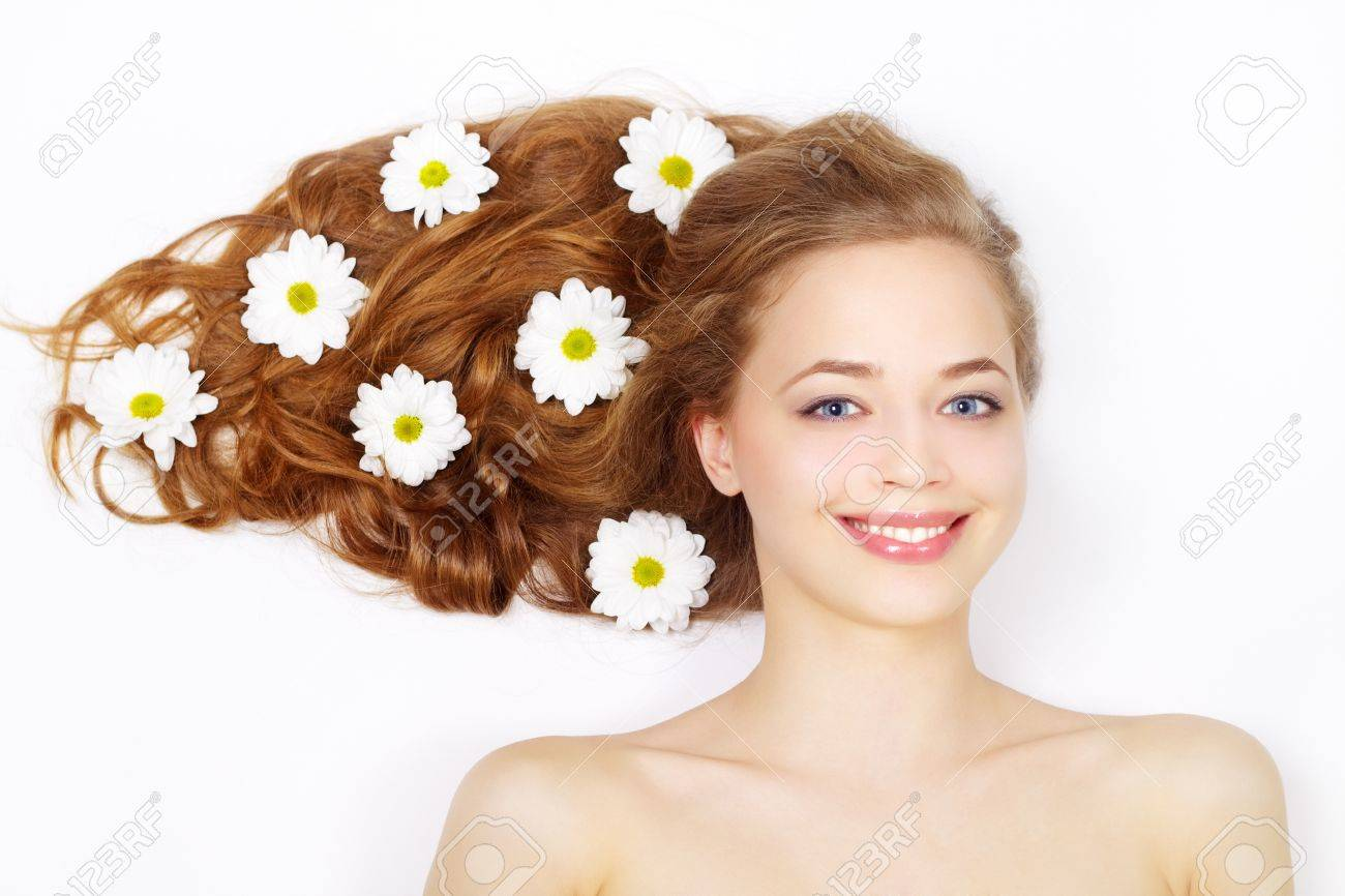 Beautiful girl with flowers in hair on a light background Stock Photo - 13230333