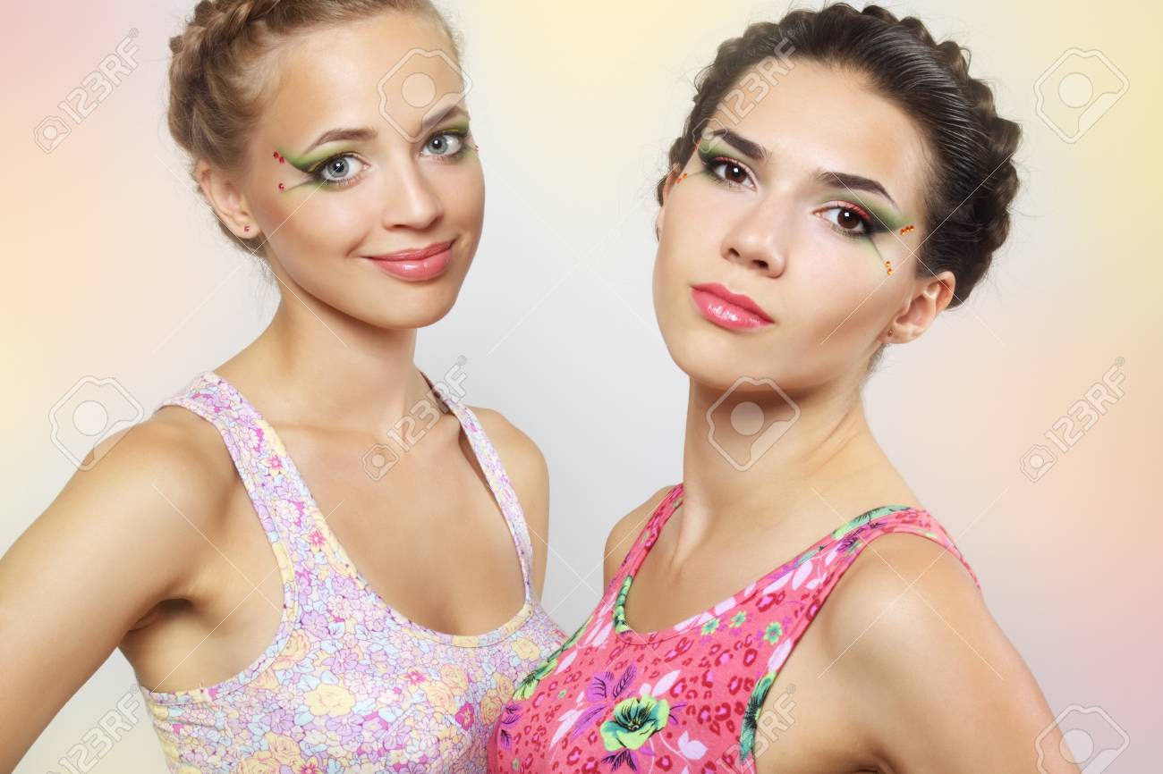 Two girls with colored make-up on light background Stock Photo - 14350746
