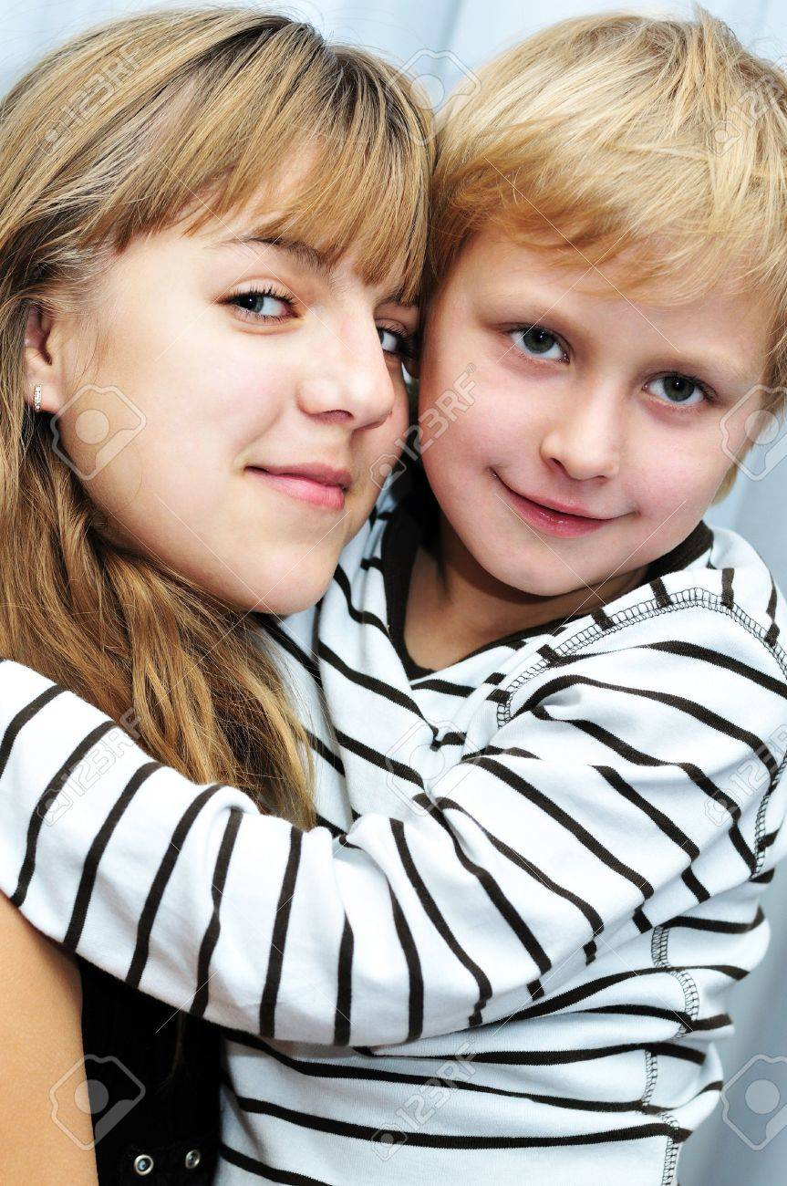 Brother and sister at home smiling and embracing Stock Photo - 6187194