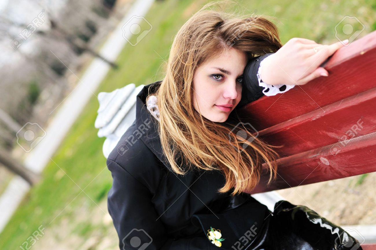 sad girl on the bench in the park stock photo picture and royalty