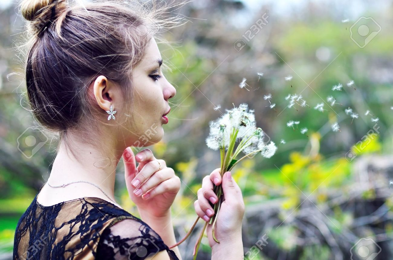 teen pretty girl blowing on many dandelions Stock Photo - 6961130