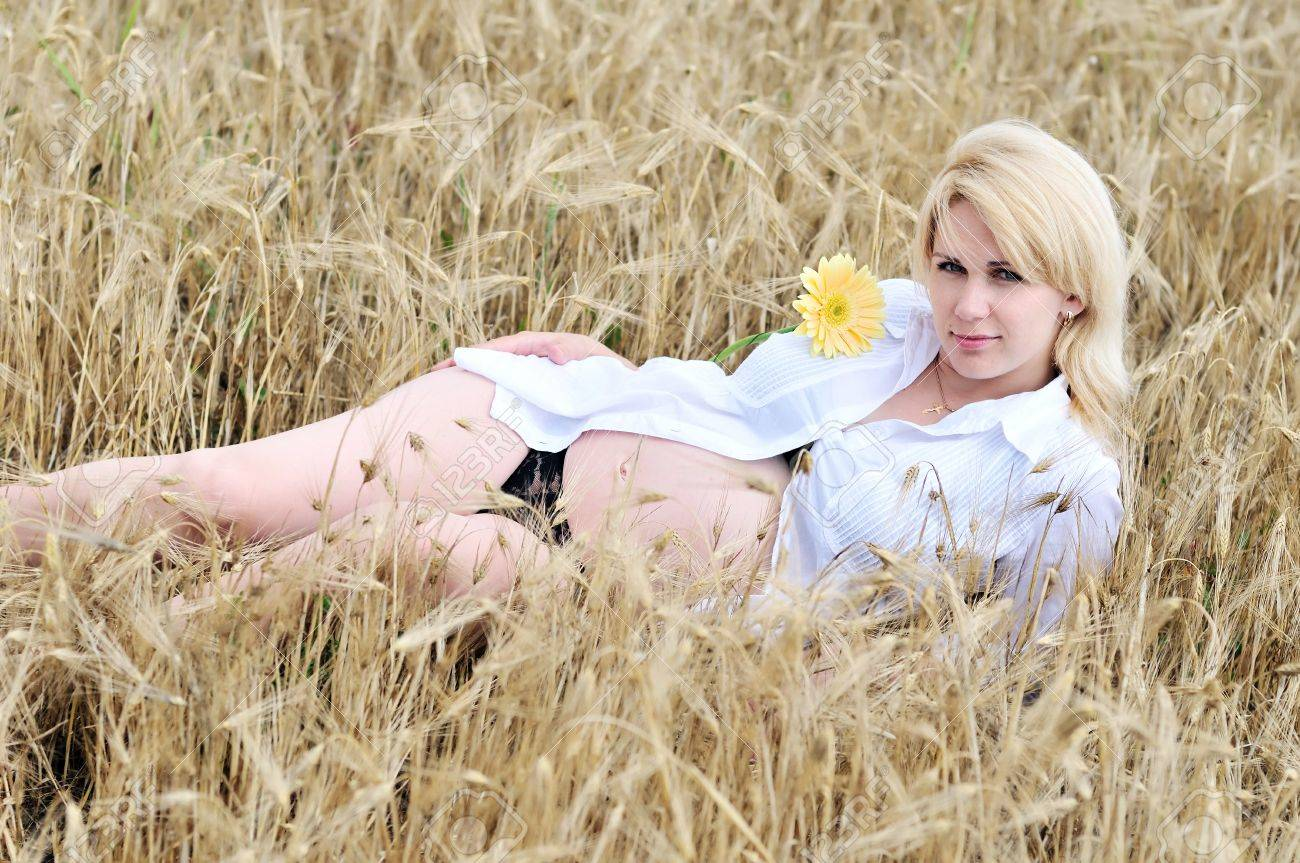pregnant beauty woman relaxing in wheat field with  gerbera Stock Photo - 7296074