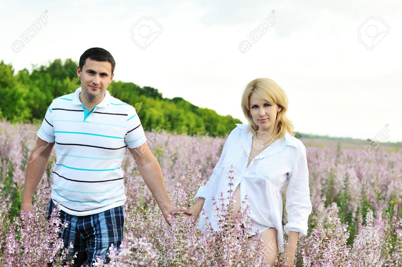 happy couple in waiting for baby walking in field Stock Photo - 7446977