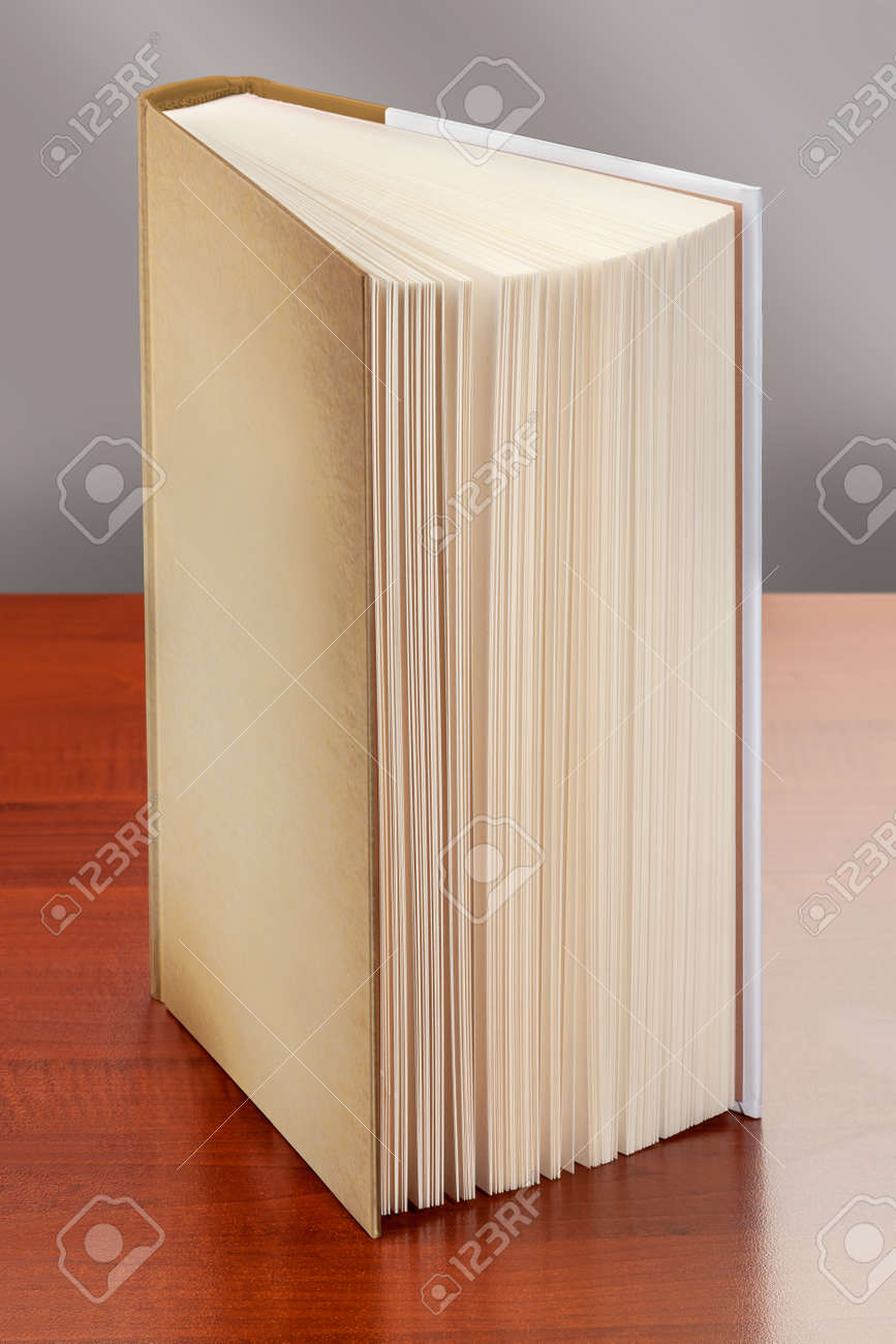 book standing upright on the table, whose pages appear to be. - 161437503