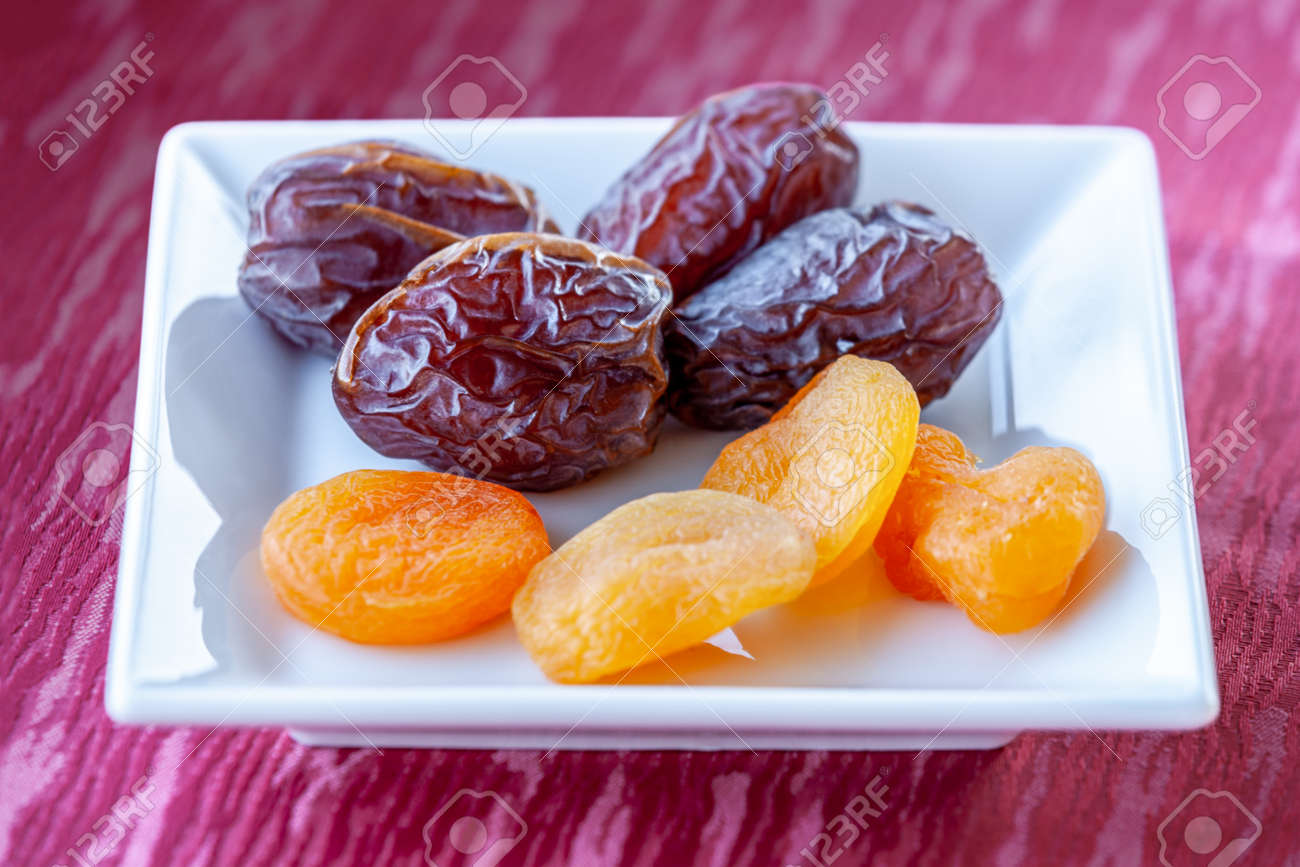 Plenty of dates and apricot arranged in a white bowl - 162919057