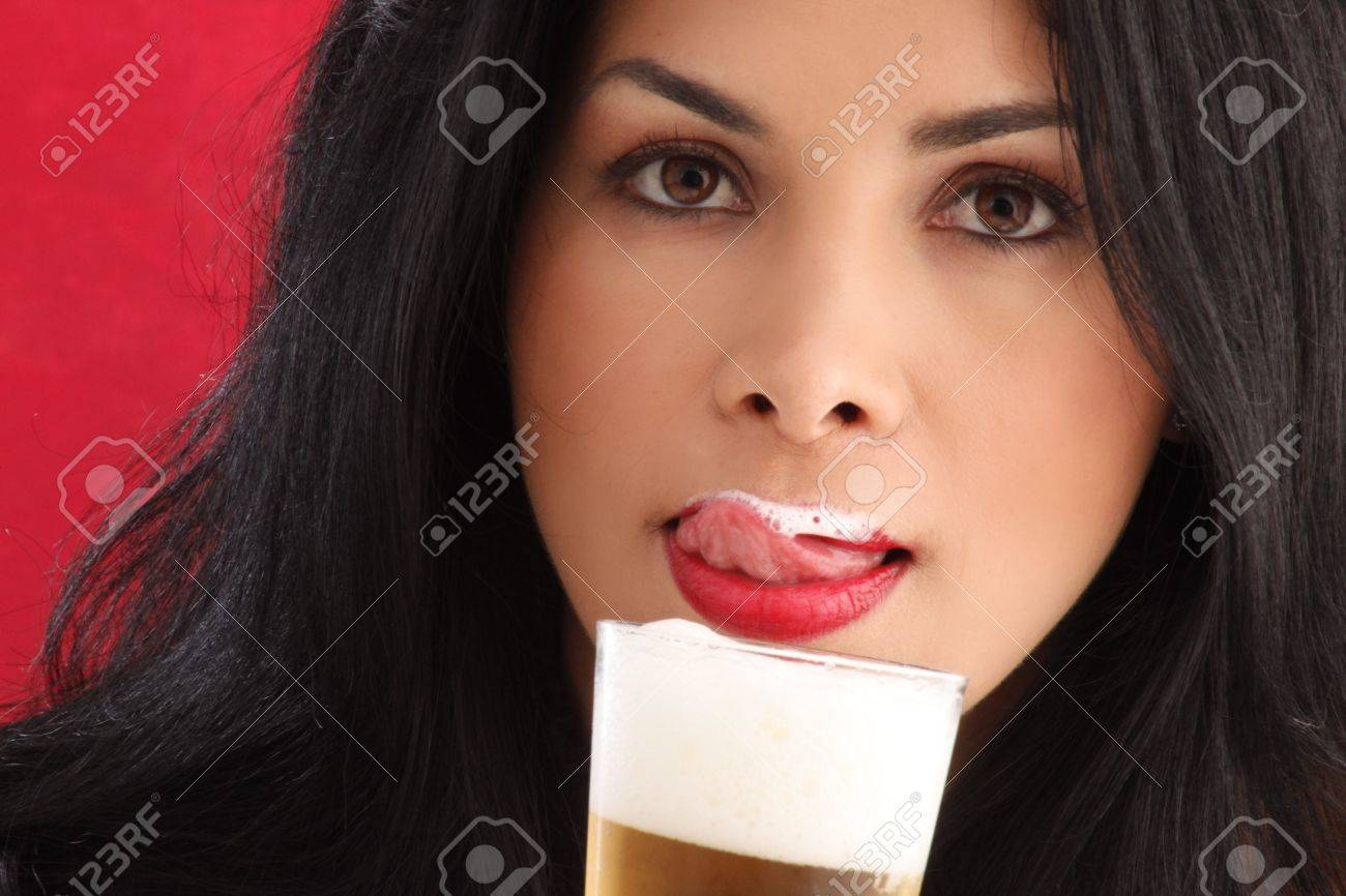 Cute brunette drinking beer and liking foam from her lips Stock Photo - 5036942