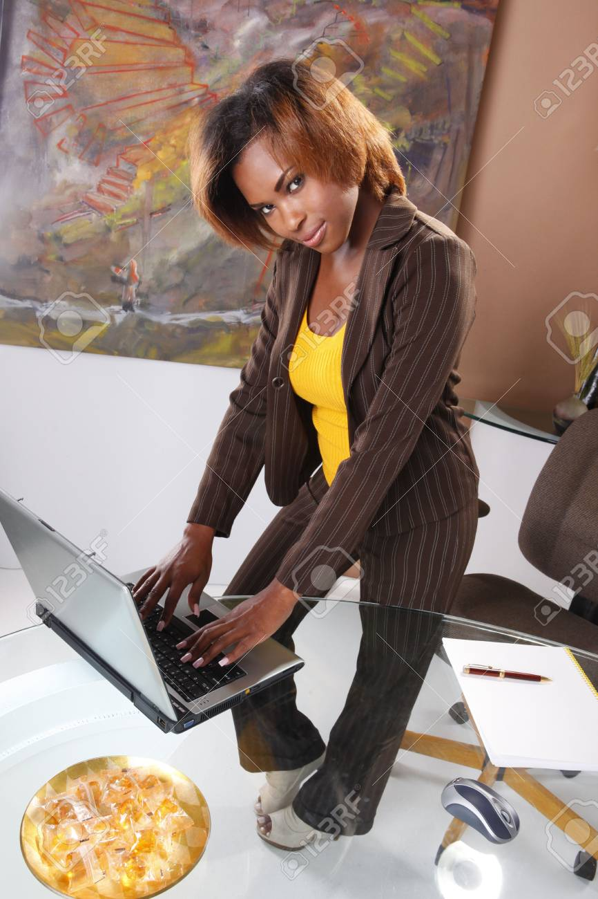 Cute executive standing at her desk Stock Photo - 7216742