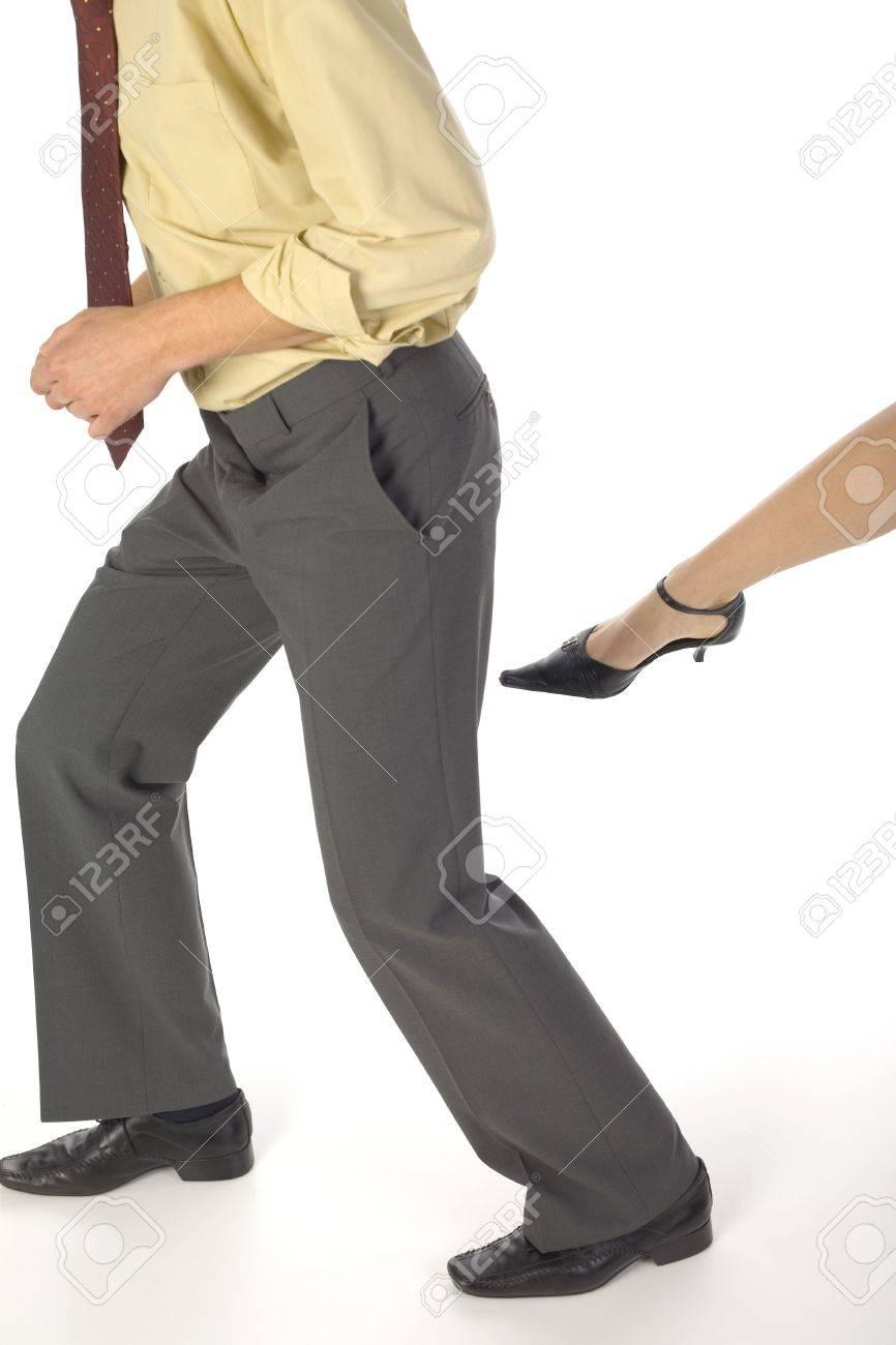 Woman's leg want to kick a businessman. White background Stock Photo - 1105852