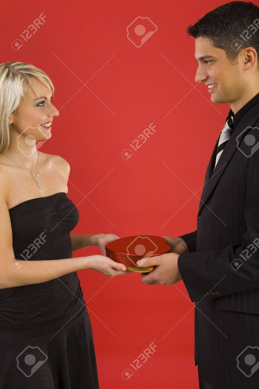 Handsome man in suit is giving beautiful woman box of chocolates. They are both smiling. Side view Stock Photo - 2610451