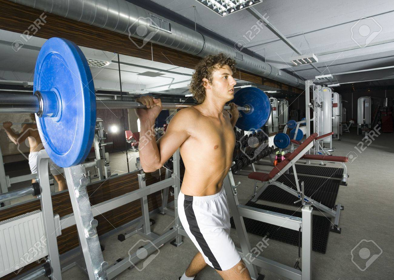 Young weightlifter with naked chest picking up heavy bar-bell. Side view Stock Photo - 2607382