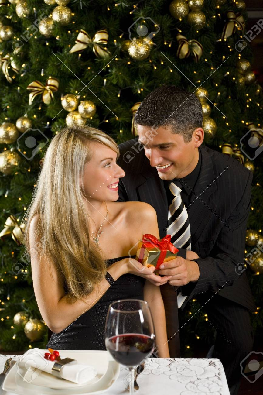 Couple at restaurant on dinner party. They giving each other a present. Front view. Stock Photo - 2651688
