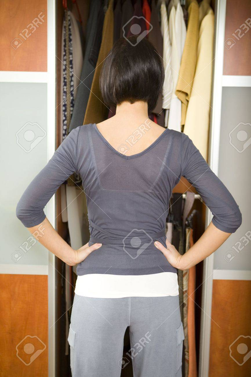 Young woman standing in front of wardrobe. She thinking what get dressed. She standing back to camera. Stock Photo - 2651654