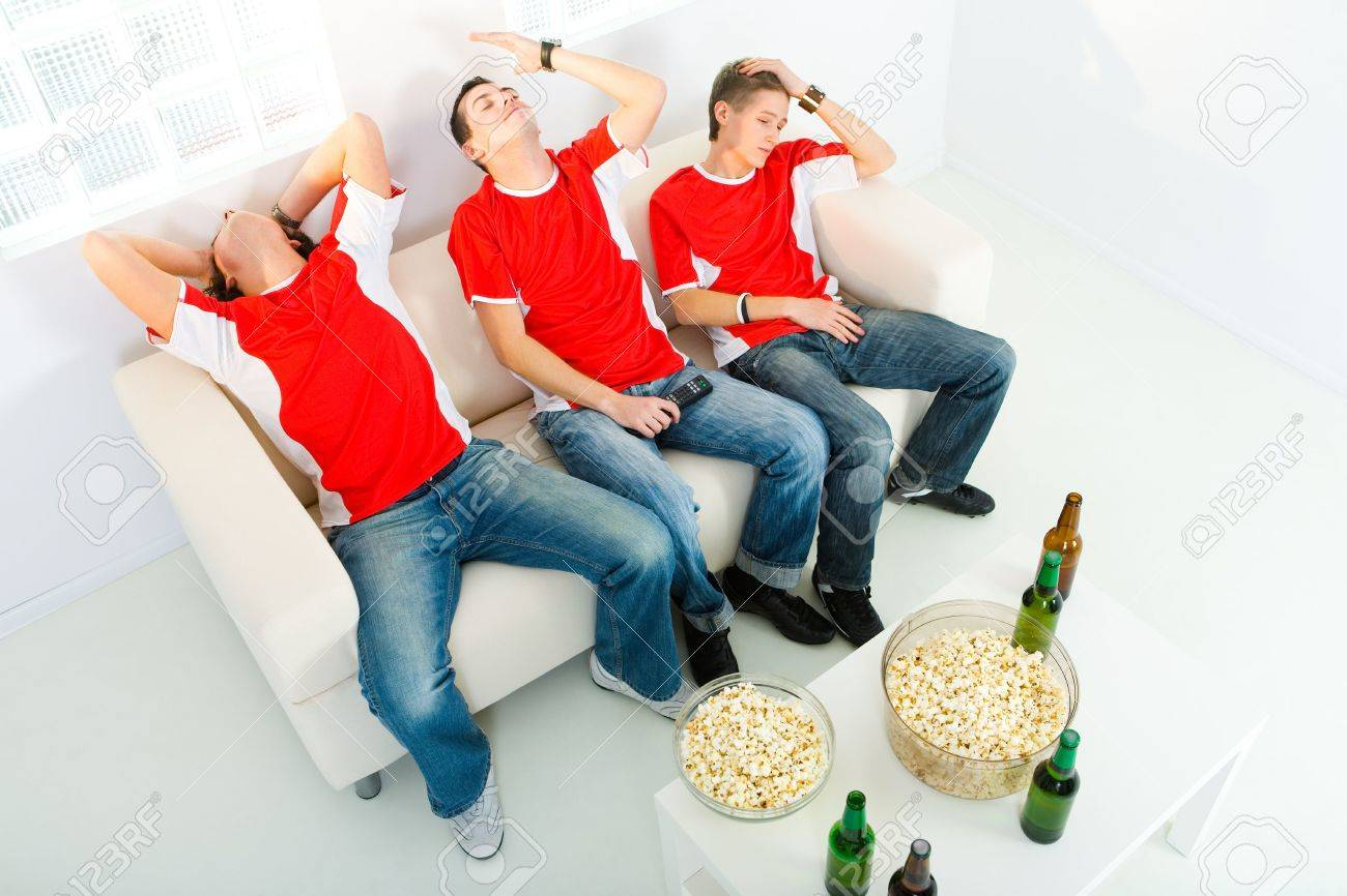 Three young men sitting on chouch and watching TV. They look disappointed. High angle view. Stock Photo - 3803681