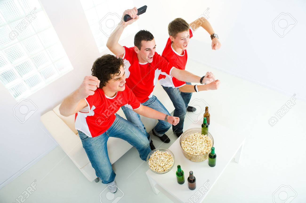 Three happy sport's fans get up from couch with raised hands. High angle view. Stock Photo - 3803666