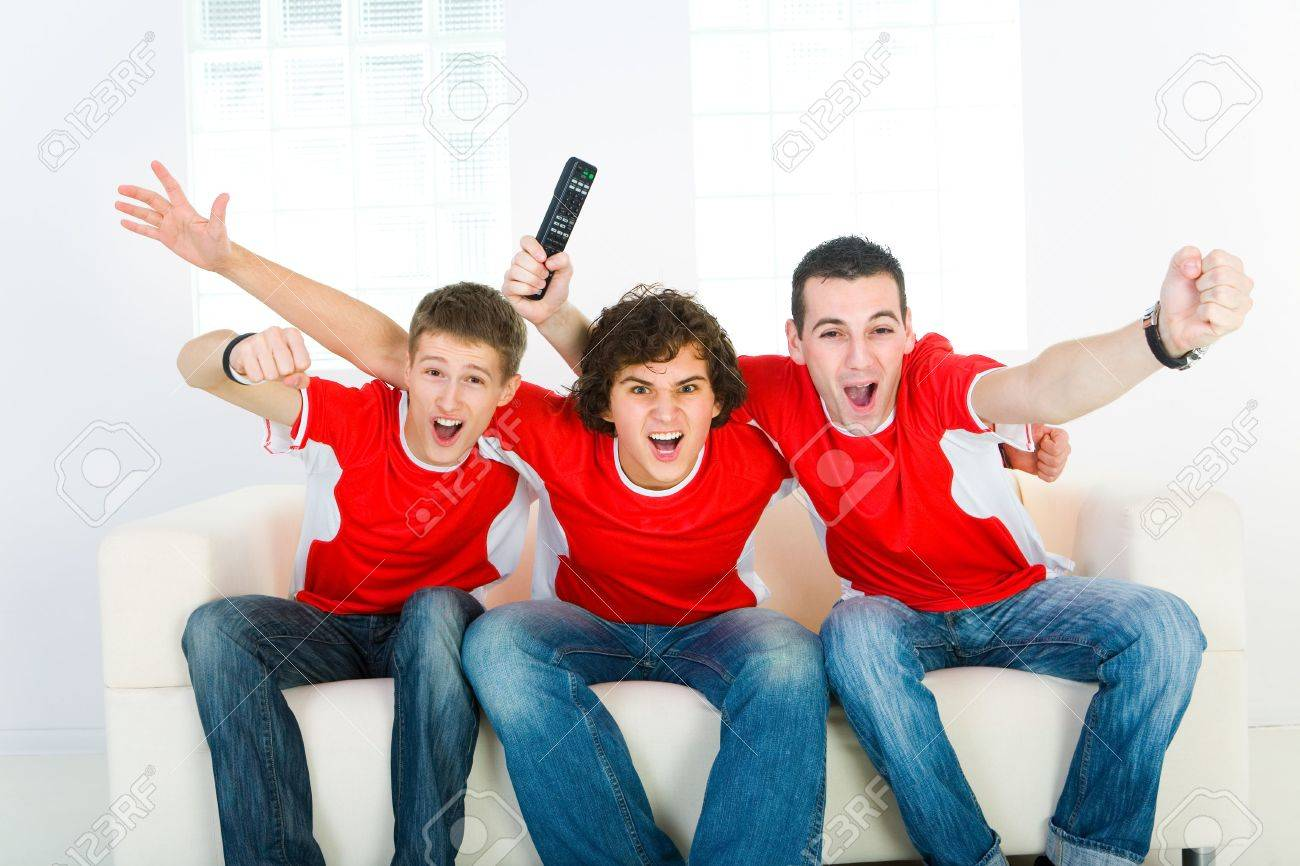 Three exciting men sitting on couch and watching sport on TV. Stock Photo - 3818008