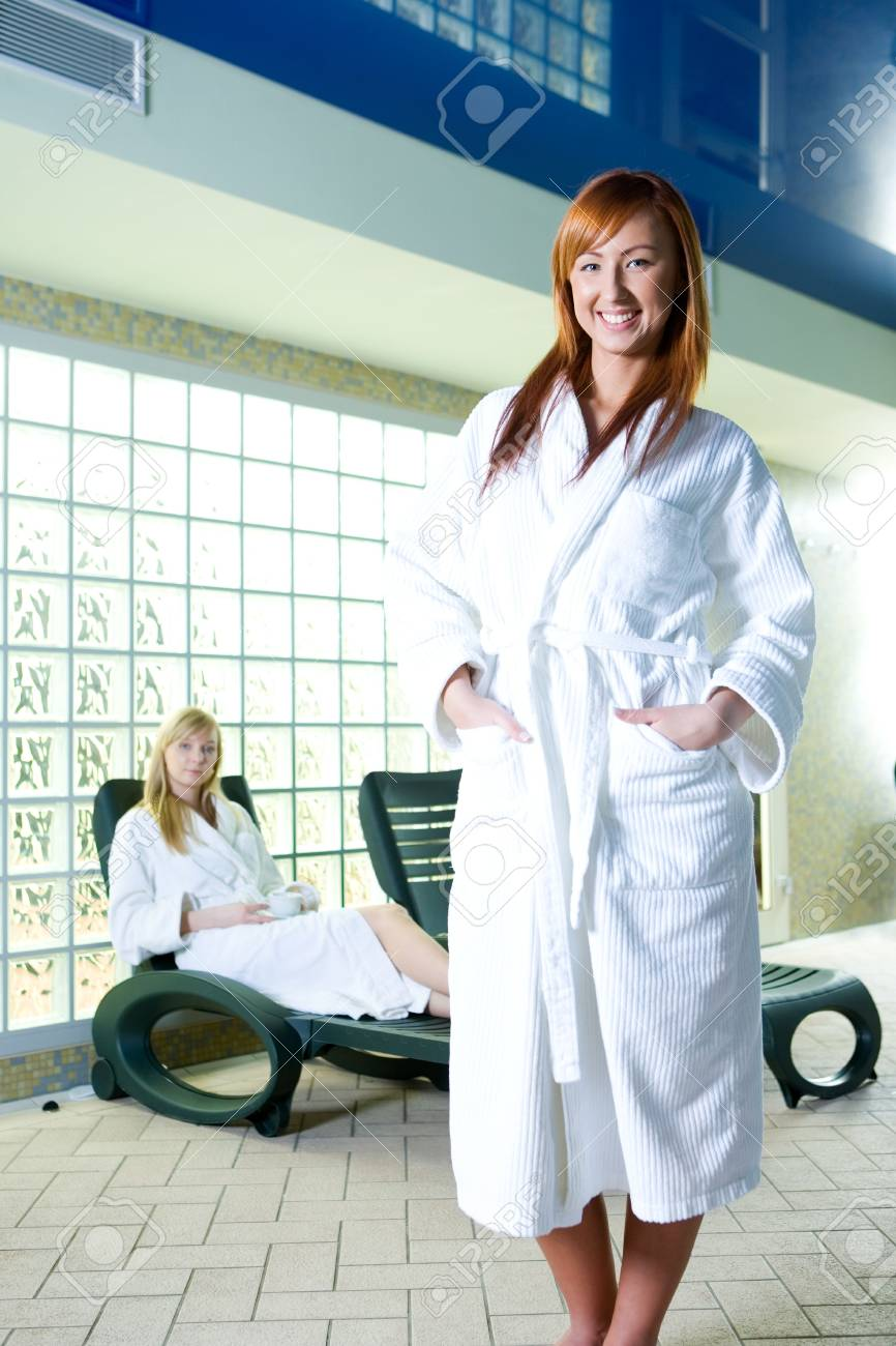 two young ladies clothed bathrobe. blonde woman sitting on deckchair