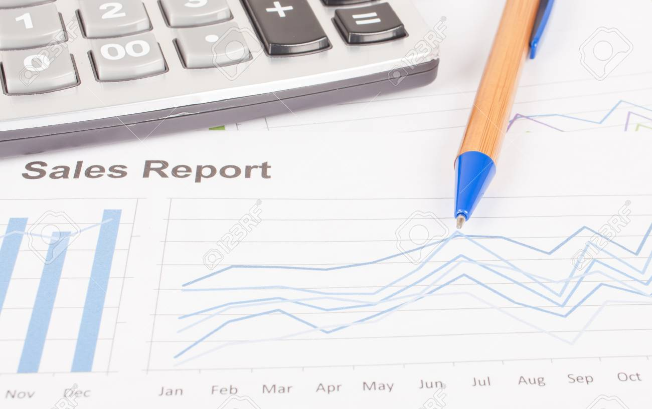 sheet of sales report with pen and calculator stock photo picture