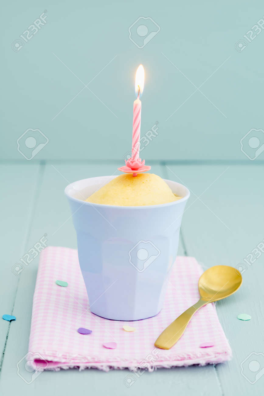 Vanilla Birthday Mug Cake In Blue With A Candle And Confetti