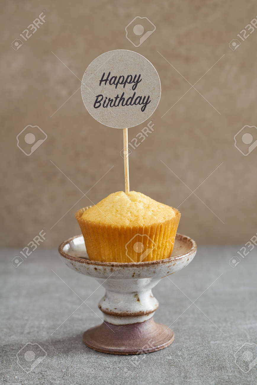 Homemade Vanilla Cupcake With A Handcrafted Birthday Cake Pick On Rustic Mini Stand Stock Photo