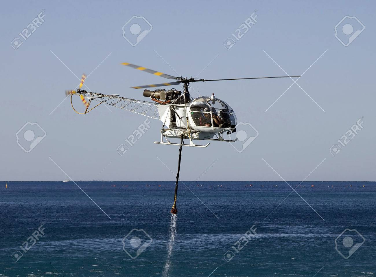 FIRE FIGHT HELICOPTER WITH WATER BUCKET AT SEA - 32203624