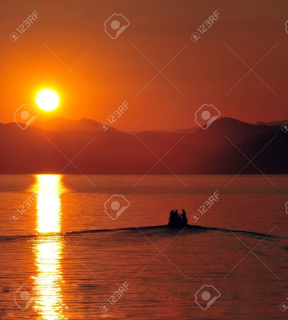 fishermen boat leaving harbour at sunset - 32754211