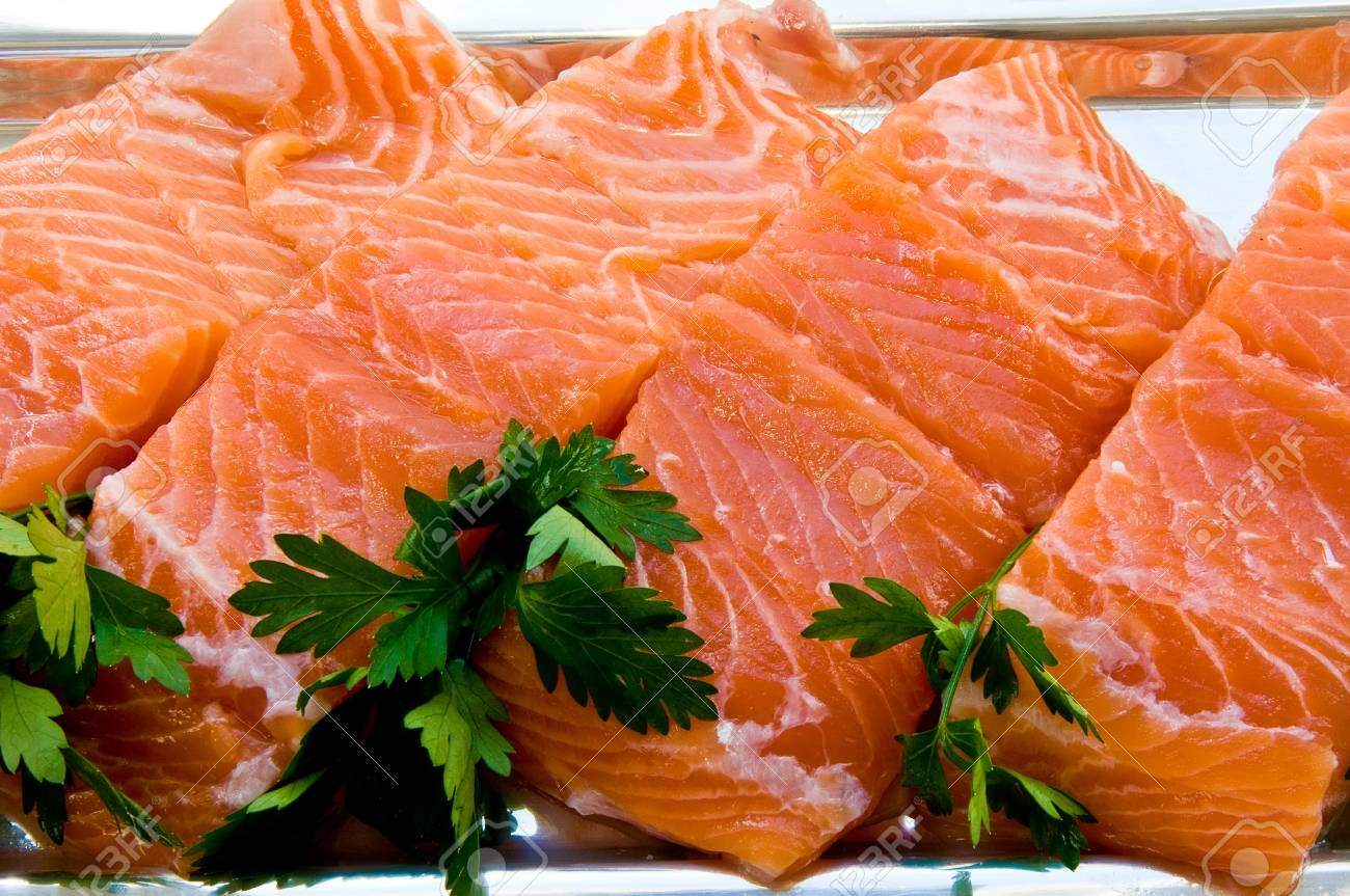 Four chunks of salmon fillet on a silver dish with parsley leaves - 33975699