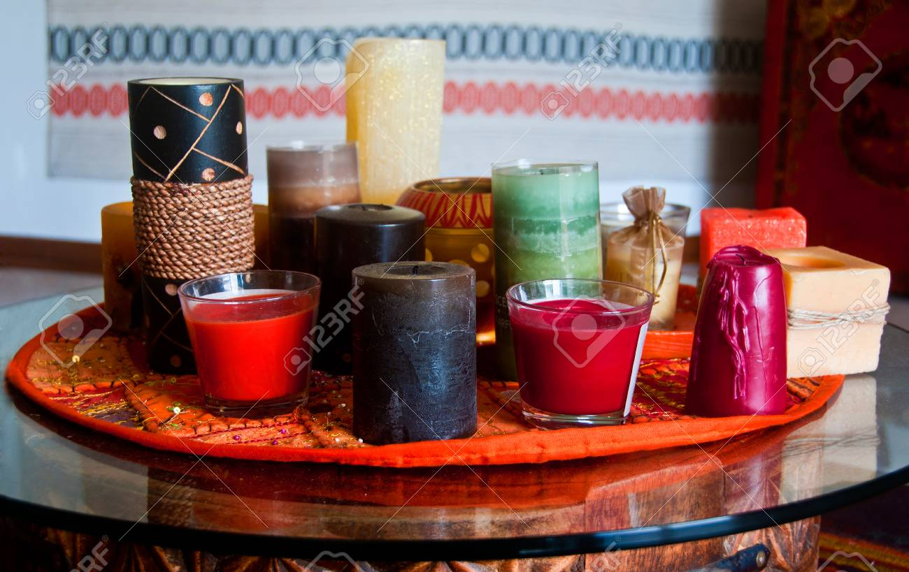 Candles of different shape and colour on a table - 33975773